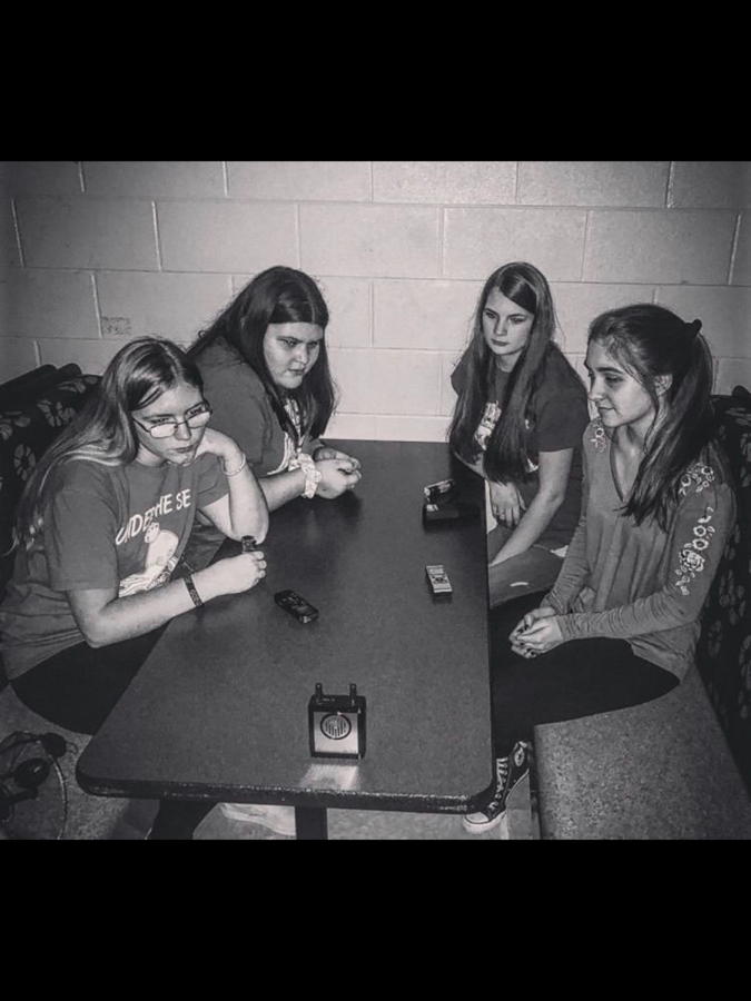 Sophomore Aubrey Wallace, Freshman Genesis Sandoval, Sophomore Kylee Grumbles, and Junior Katie Bilka sit in the cafeteria with their equipment during Paranormal Society.